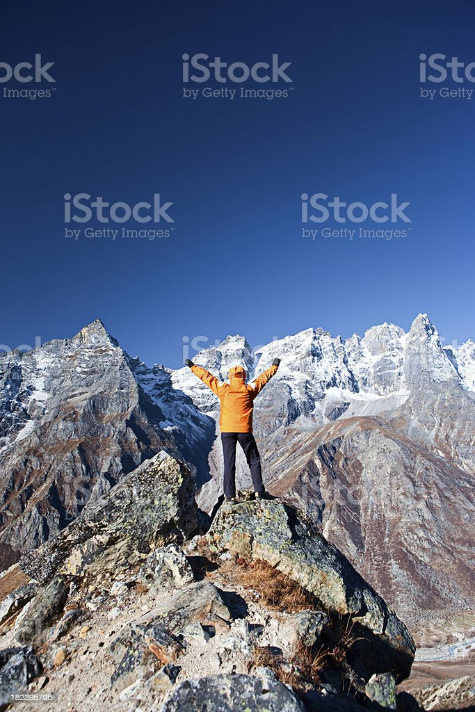 Female trekker lifts her arms in victory, Himalayas royalty-free stock photo