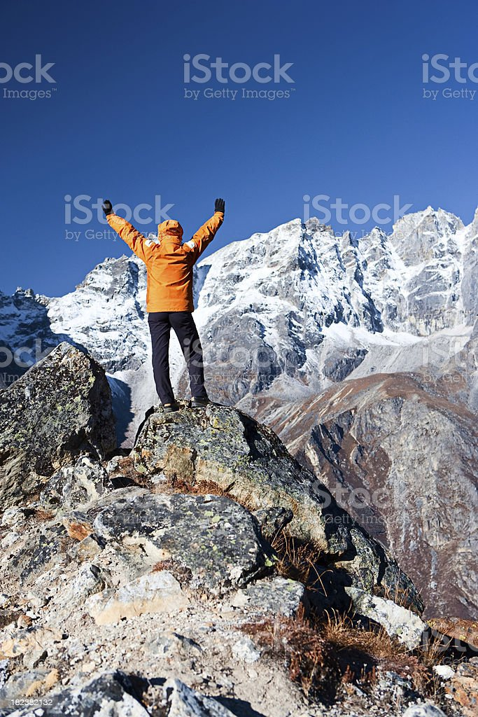 Female trekker lifts her arms in victory, Himalyas stock photo