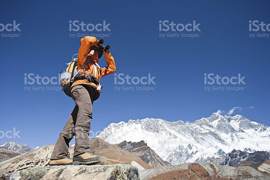 Female trekker looking through binoculars, Lhotse in background. royalty-free stock photo