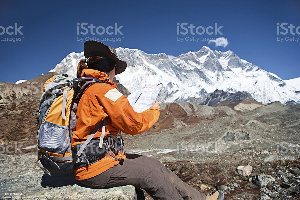 Female trekker studying a map, Lhotse in background royalty-free stock photo