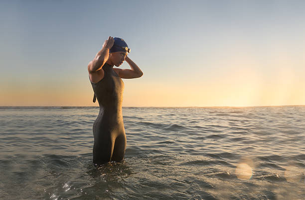 Female Triathlon Athlete at Sunrise Female Triathlon Athlete putting her goggle on at Sunrise. wetsuit stock pictures, royalty-free photos & images