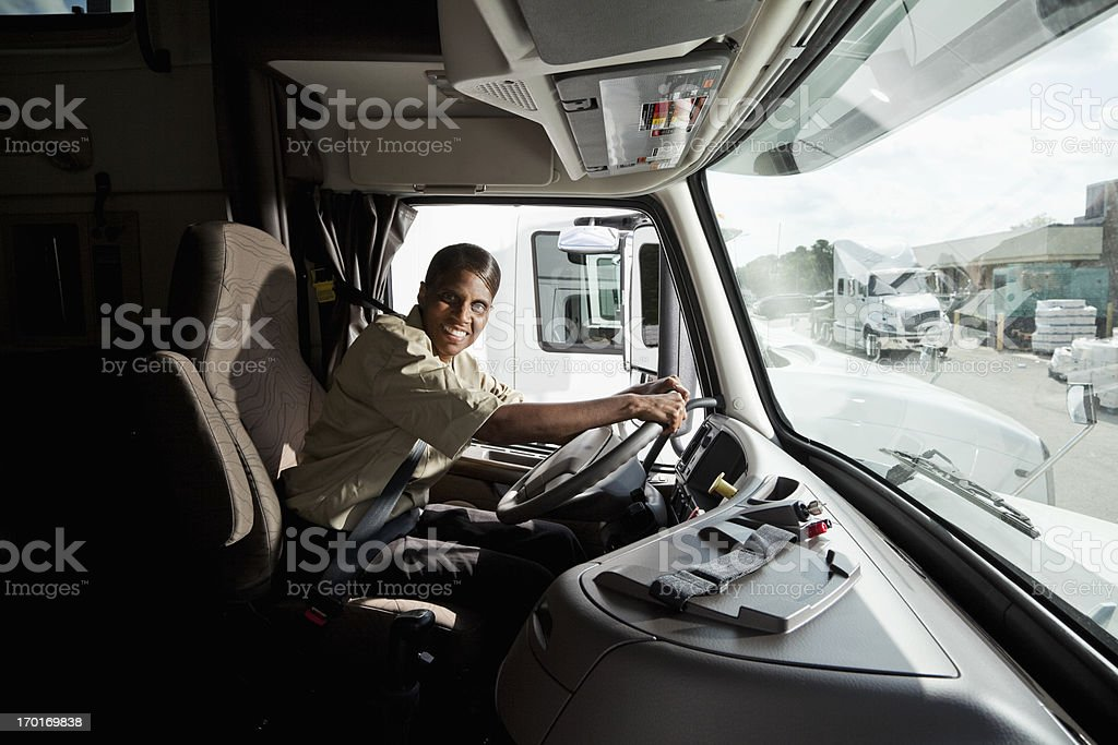 Female truck driver sitting in cab of semi-truck royalty-free stock photo