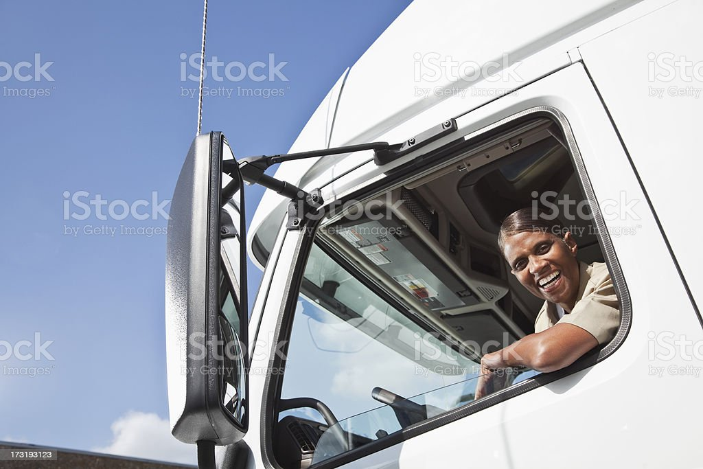 Female truck driver sitting in cab of semi-truck stock photo
