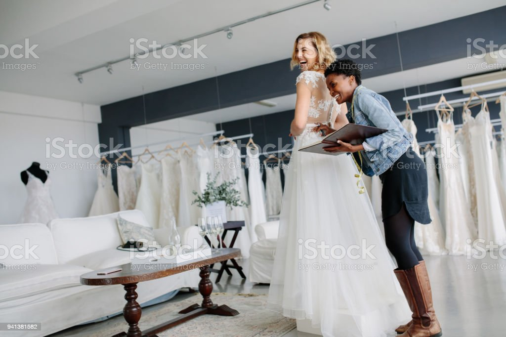 Female trying on wedding gown with women assistant in shop stock photo