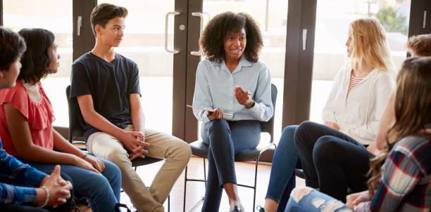 weiblich-tutor führenden diskussionsgruppe unter gymnasiasten - sprachunterricht stock-fotos und bilder