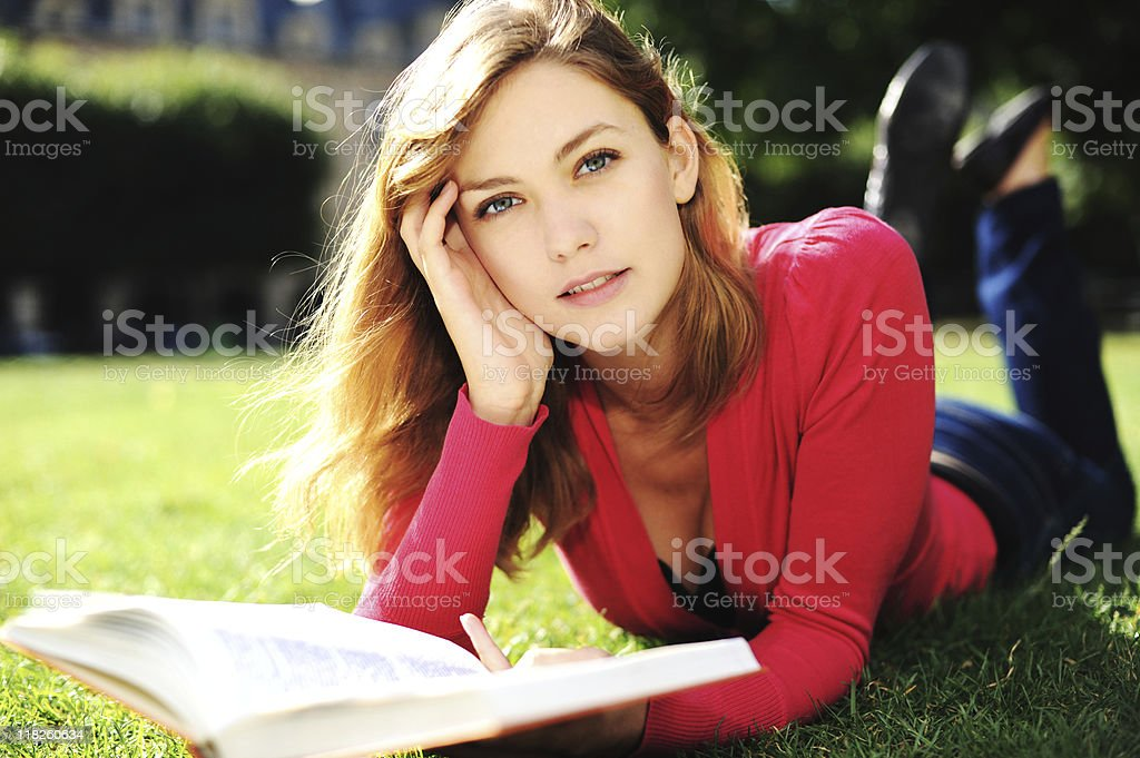 Female University Student Reading Textbook on Lawn royalty-free stock photo