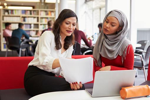 Female University Student Working In Library With Tutor - Fotografie stock e altre immagini di Abbigliamento casual