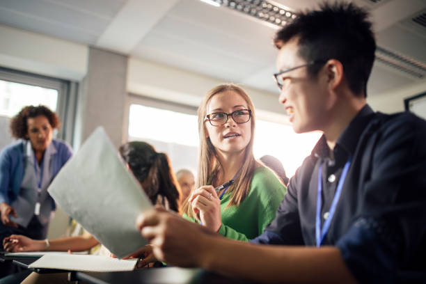 female university students discuss presentation, very real - debate стоковые фото и изображения