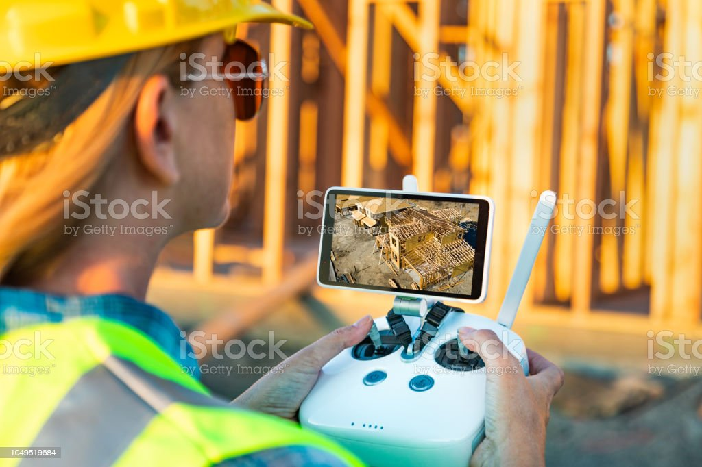 Female Unmanned Aircraft System (UAV) Quadcopter Drone Pilot with Controller Inspecting New House Framing stock photo