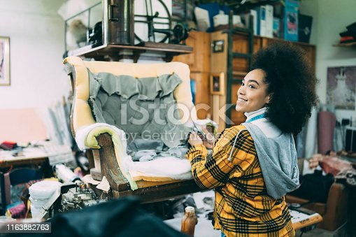 African woman renovating old furnitures in upholstery studio.