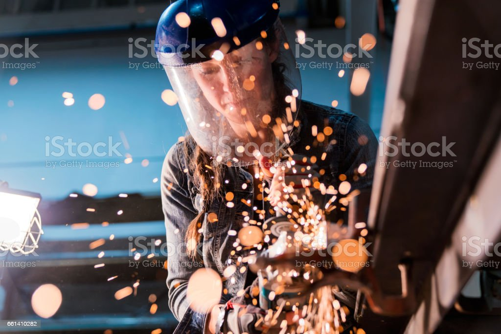 Female using angle grinder in workshop stock photo