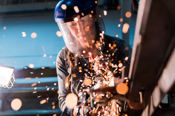 Female using angle grinder in workshop Female welder working in her workshop using an angle grinder. Los Angeles, America. October 2016 metalwork stock pictures, royalty-free photos & images
