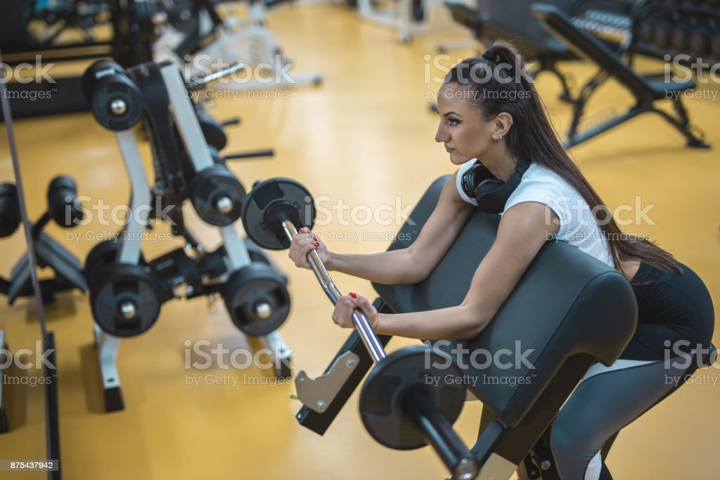 Female using barbell for bicep exercises stock photo