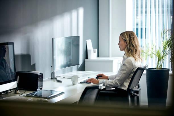 オフィスでコンピュータを使用する女性 - オフィスチェア ストックフォトと画像