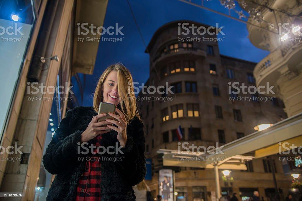 Female using her mobile phone, city skyline night light background photo libre de droits