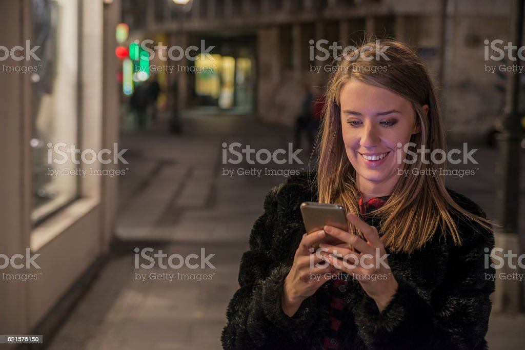 Female using her mobile phone, city skyline night light background photo libre de droits