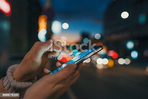 istock Female using her mobile phone, city skyline night light background 898878350