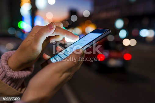 622971132istockphoto Female using her mobile phone outside at night 899227090