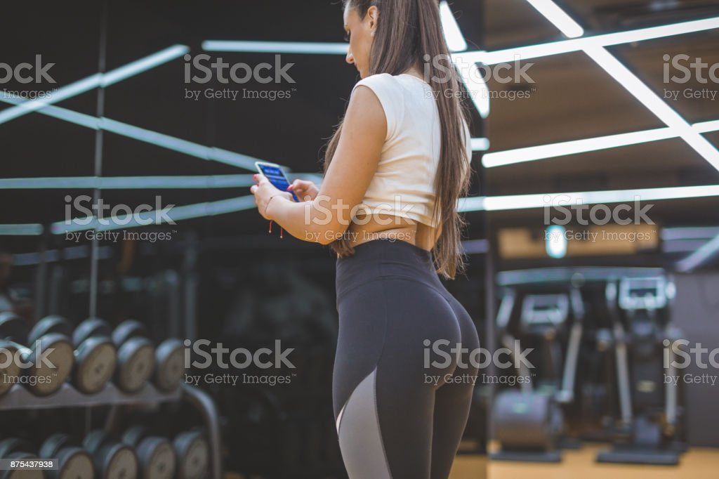 Female using smart phone in a gym stock photo