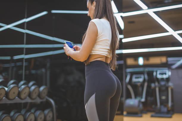 mujer con el teléfono inteligente en un gimnasio - buenos culos fotografías e imágenes de stock
