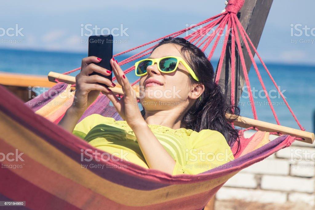 Female using smartphone in hammock stock photo