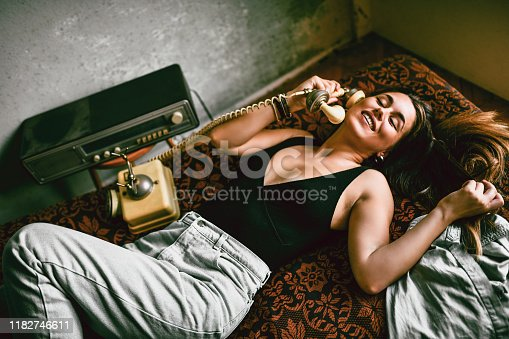Female Using Vintage Telephone While Relaxing On Bed