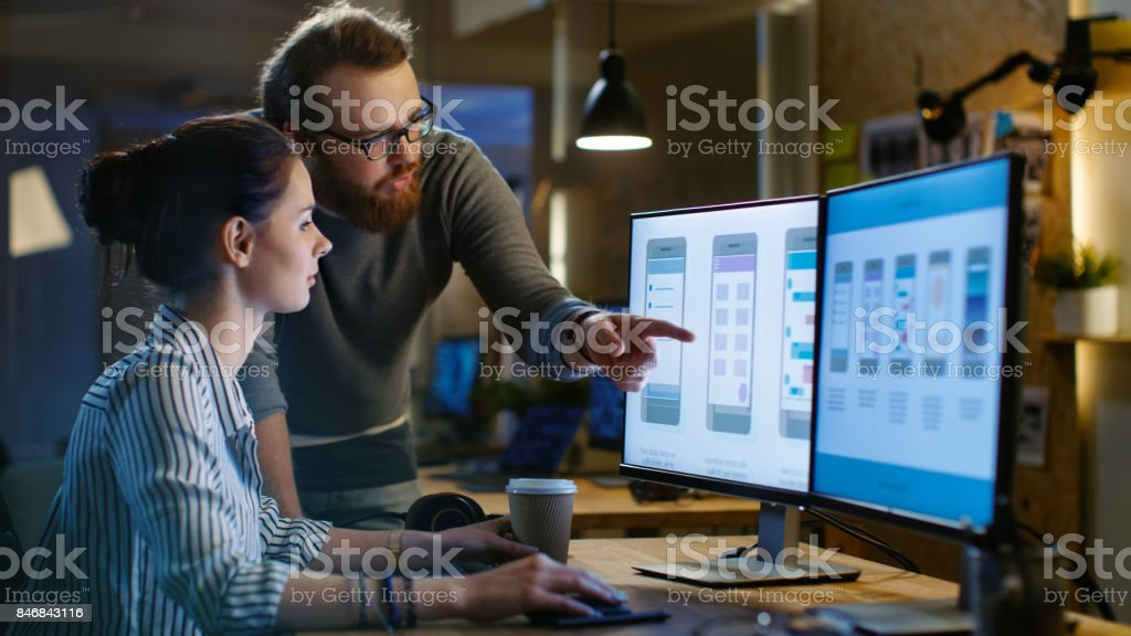 Female UX Architect Has Discussion with Male Design Engineer, They Work on Mobile Application Late at Night, She Drinks Coffee. In the Background Wall with Project Sticky Notes and Other Studio Employees. stock photo
