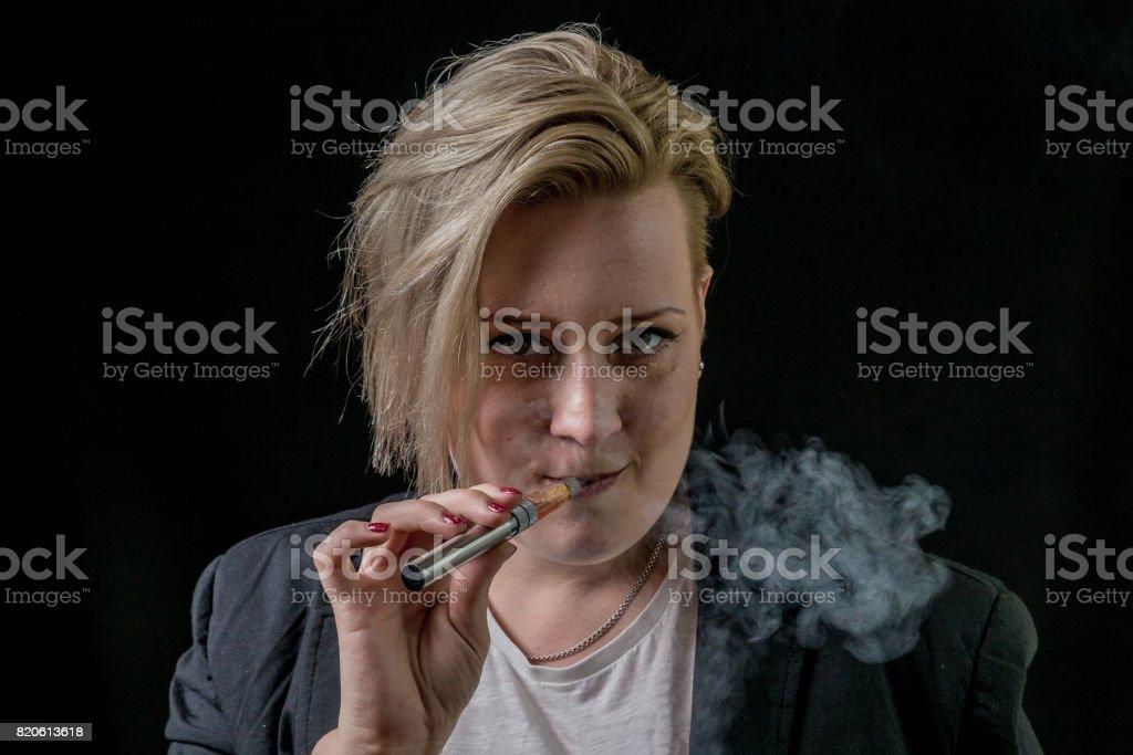 Female vaping vaporizer and facing camera stock photo