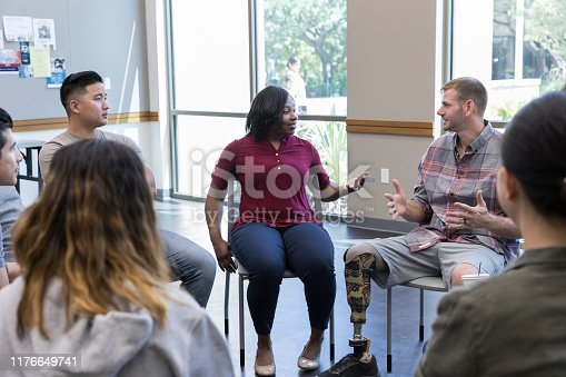 African American female veteran gestures while discussing an event with a male veteran during a group therapy session.