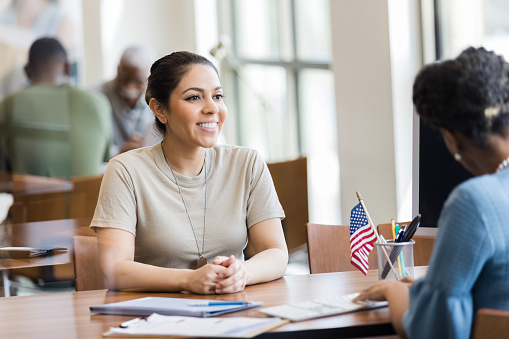 A cheerful mid adult female soldier smiles as she talks with a bank employee about a home loan.