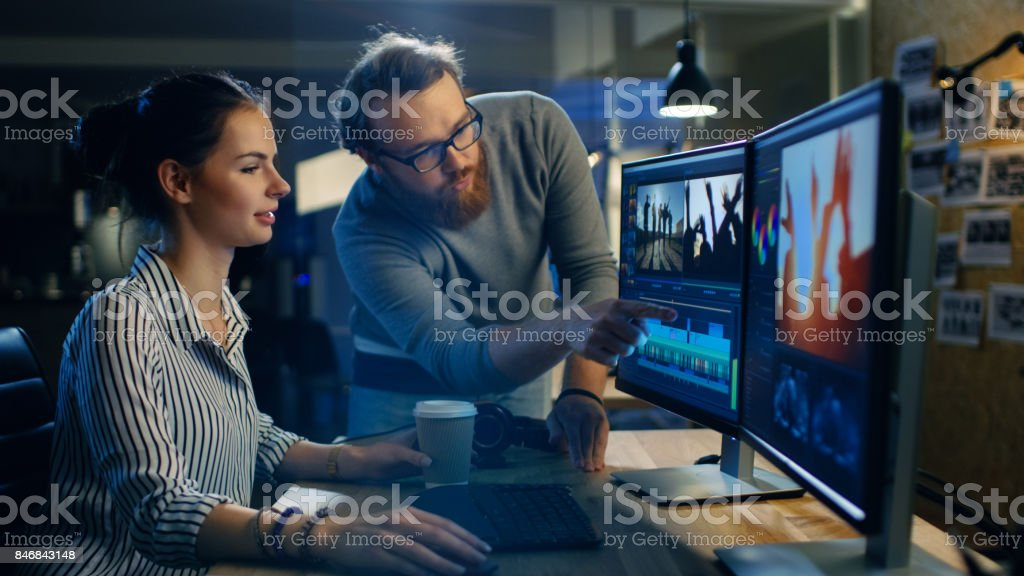 Female Video and Sound Editor Works With Her Male Colleague on a Project on Her Personal Computer with Two Displays. They Work in a Creative Loft Office. stock photo