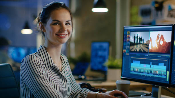 Female Video Editor Turns and Warmly Smiles into the Camera. Her Office is Modern and Creative Loft Studio. stock photo