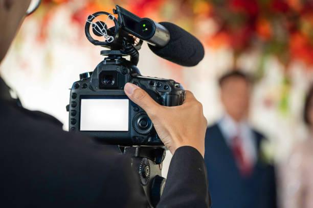 weibliche videografin im backside sind shooing und aufzeichnung video in wedding event. - wedding photography and videography stock-fotos und bilder