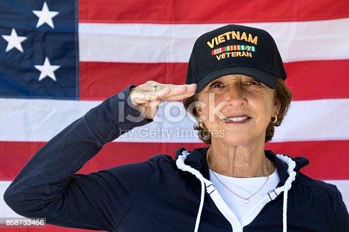 istock Female Vietnam Veteran Saluting  looking content wearing Veterans cap, with American Flag in background. 858733456