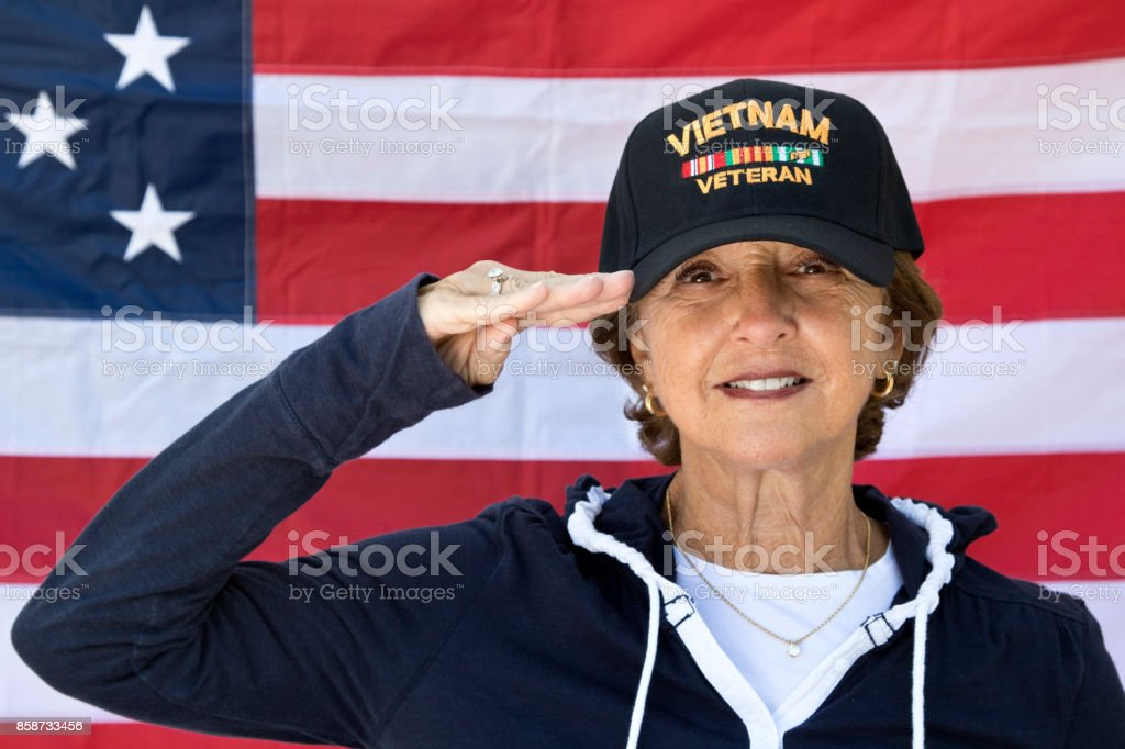 Female Vietnam Veteran Saluting  looking content wearing Veterans cap, with American Flag in background. stock photo