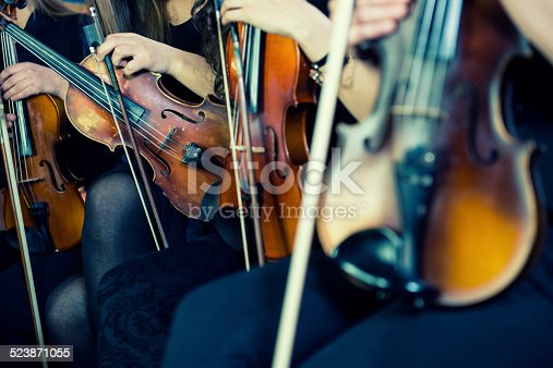 Symphony music, violinists at concert, hand close up.