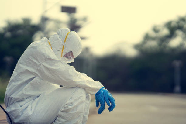 Female virologist, wearing PPE. She is feeling hopeless and tired. stock photo