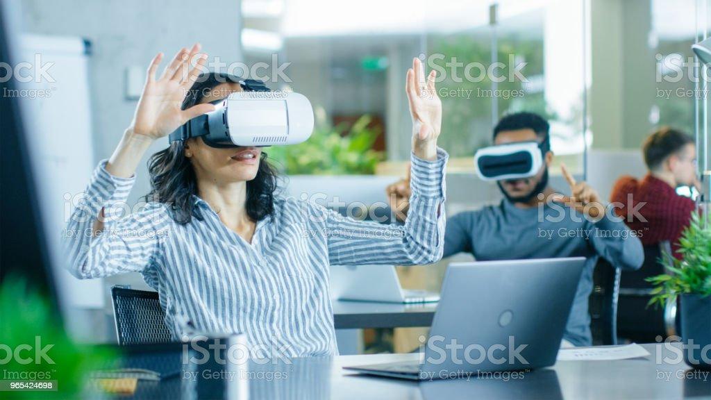 Réalité virtuelle femme Ingénieur / développeur portant le casque de réalité virtuelle crée du contenu avec ses collègues. Brillantes jeunes travaux relatifs au projet de réalité augmentée & mixtes. - Photo de Adulte libre de droits