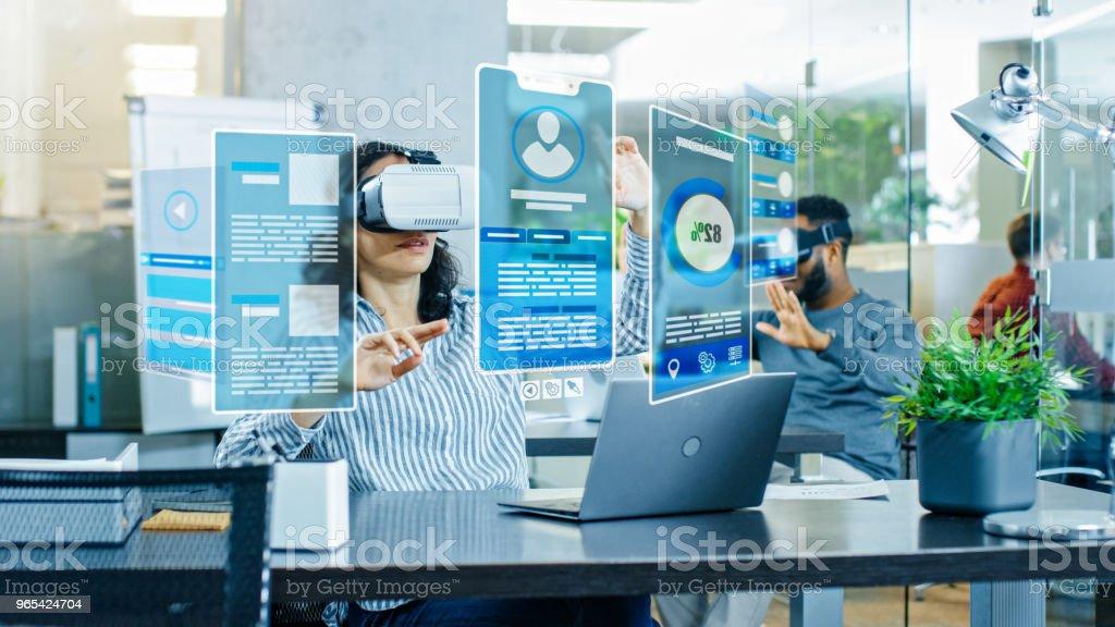 Réalité virtuelle femme Ingénieur / développeur portant le casque de réalité virtuelle crée du contenu avec ses collègues. Brillantes jeunes travail avec des hologrammes dans le projet de réalité augmentée & mixtes. - Photo de Adulte libre de droits