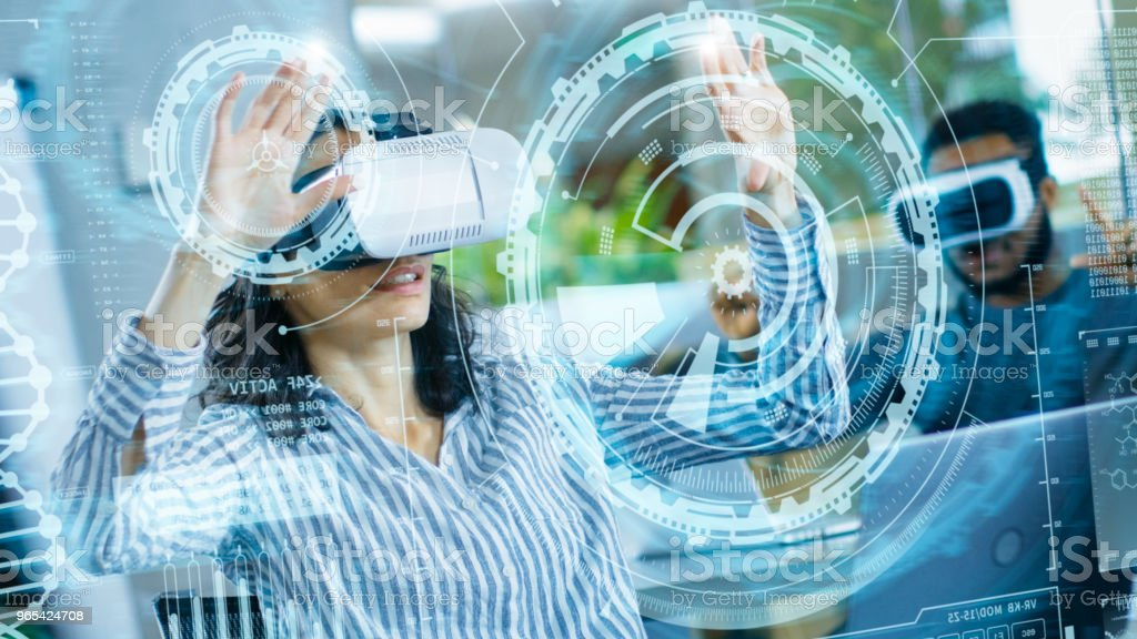 Female Virtual Reality Engineer/ Developer Wearing Virtual Reality Headset Creates Content With Her Colleagues. Bright Young People Work with Holograms in Augmented & Mixed Reality Project. royalty-free stock photo