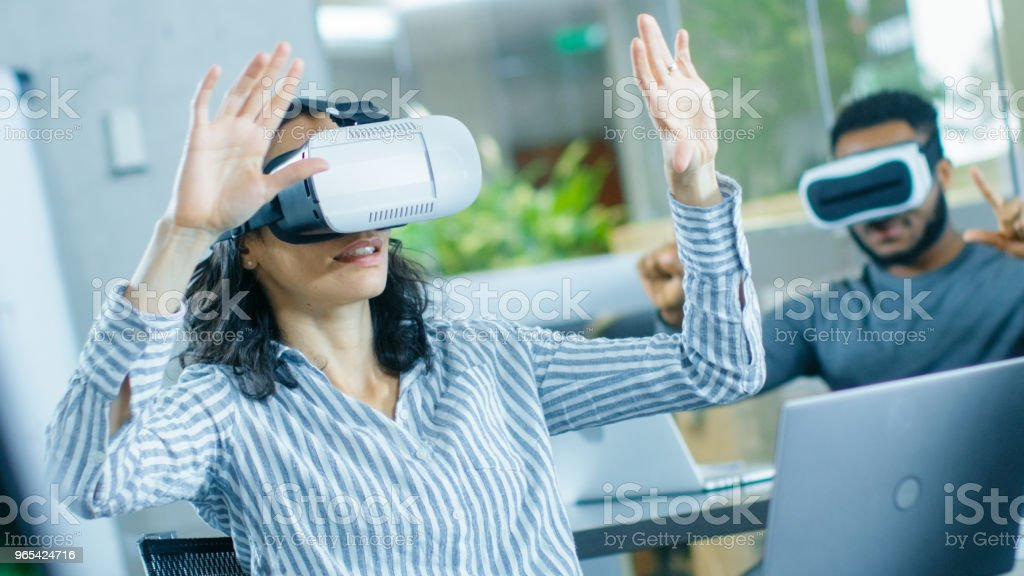 Female Virtual Reality Engineer/ Developer Wearing Virtual Reality Headset Creates Content With Her Colleagues. Creative Young People Work on the Augmented & Mixed Reality Project. royalty-free stock photo