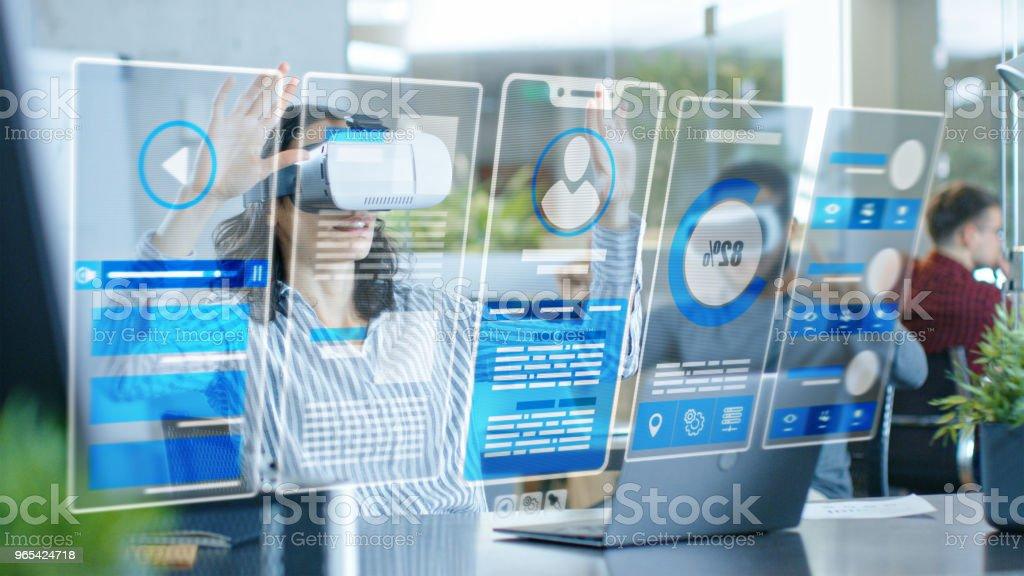 여성 가상 현실 엔지니어 / 개발자 가상 현실 헤드셋을 입고 그녀의 동료와 함께 콘텐츠를 만듭니다. 밝은 젊은 사람들이 홀로그램 증강 및 혼합 현실 프로젝트에서 작업. - 로열티 프리 2명 스톡 사진