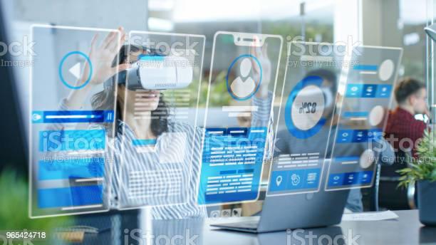 Foto de Engenheiro De Realidade Virtual Feminino Desenvolvedor Usando Realidade Virtual Fone Cria Conteúdo Com Seus Colegas Brilhantes Jovens Trabalho Com Hologramas No Projeto De Realidade Aumentada E Misturada e mais fotos de stock de Adulto