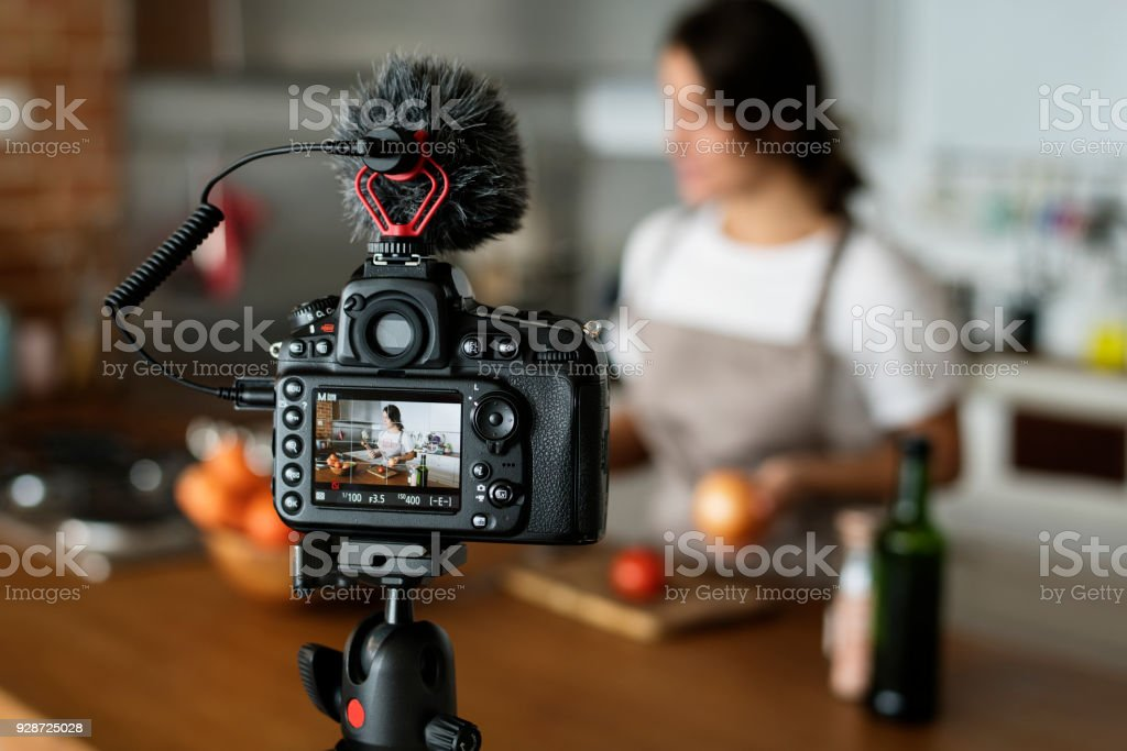 Female vlogger recording cooking related broadcast at home - Zbiór zdjęć royalty-free (Aparat fotograficzny)
