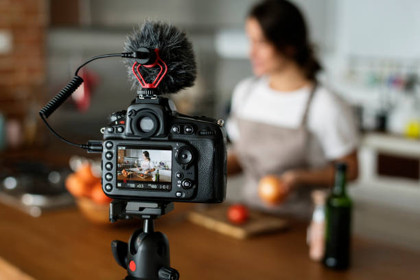 Female vlogger recording cooking related broadcast at home stock photo
