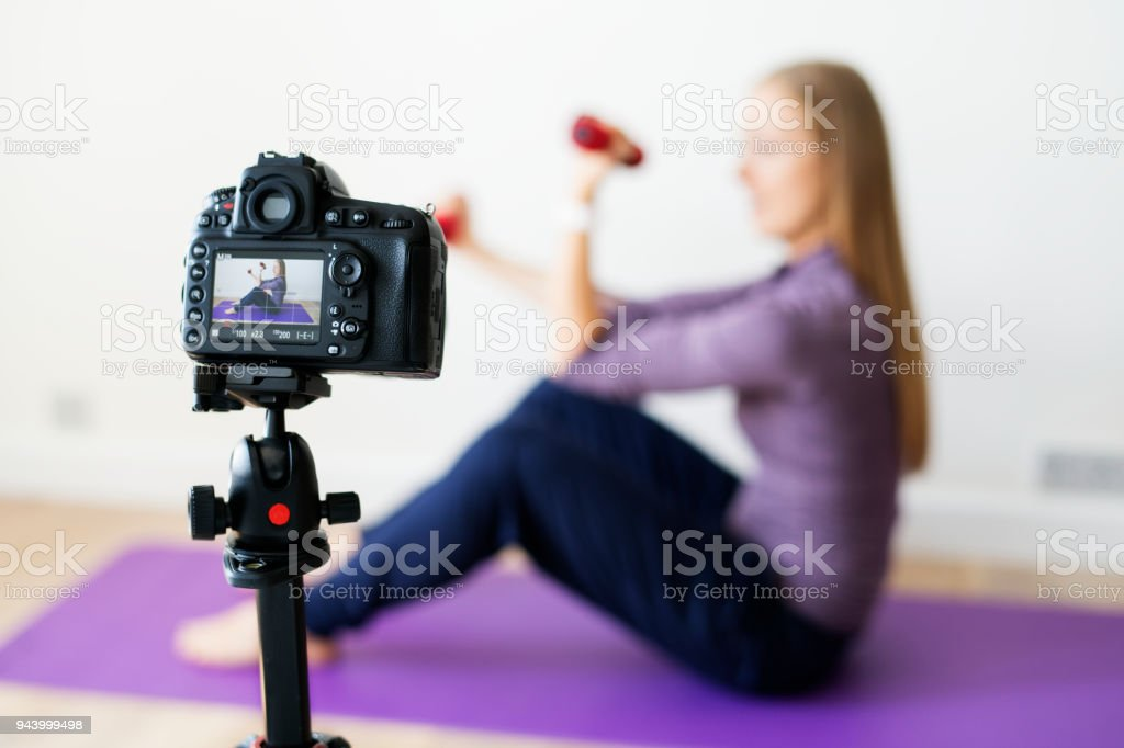 Female vlogger recording sports related broadcast at home stock photo
