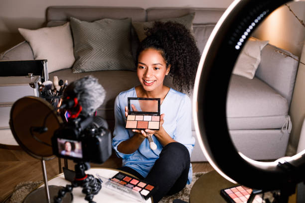female vlogger showing cosmetic accessories while recording content - side hustle stock pictures, royalty-free photos & images