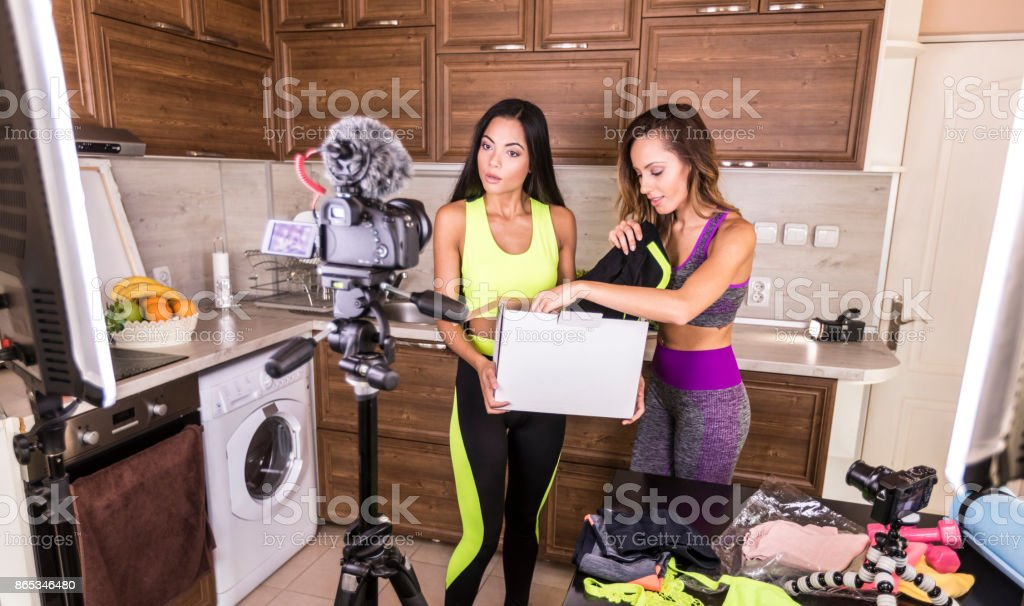 Female vloggers unpacking box with sportswear stock photo