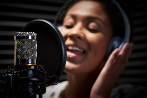 Female Vocalist Wearing Headphones Singing Into Microphone In Recording Studio Female Vocalist Wearing Headphones Singing Into Microphone In Recording Studio diva human role stock pictures, royalty-free photos & images