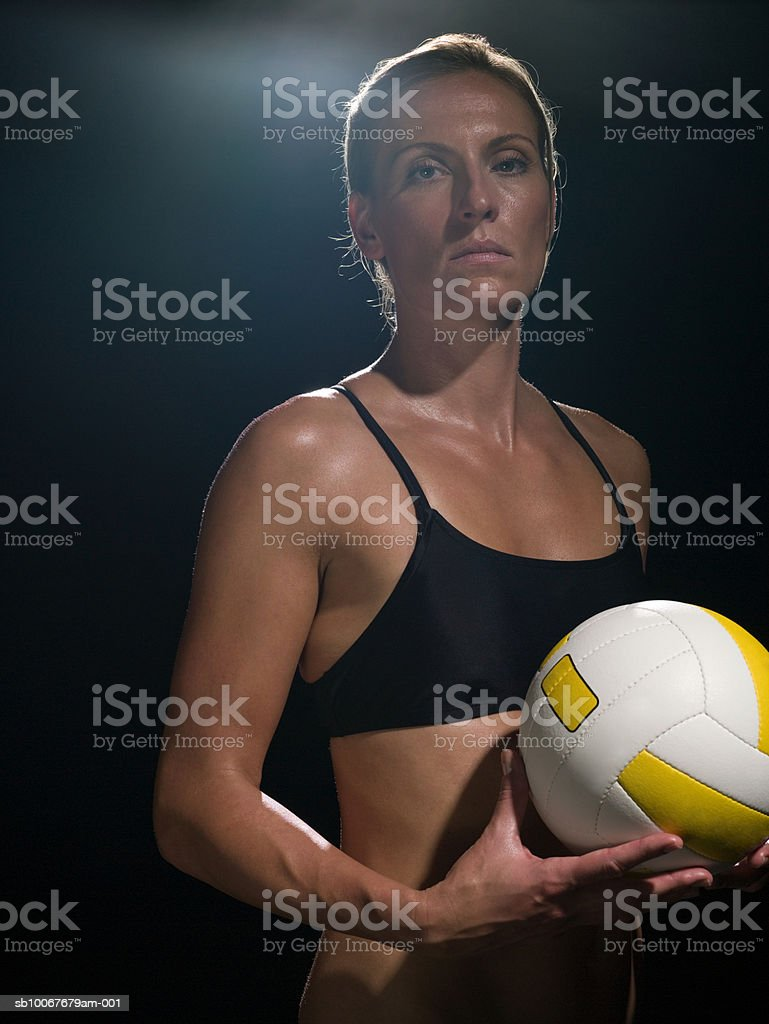 Female volleyball player holding ball, portrait 免版稅 stock photo